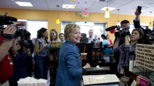 Democratic presidential candidate Hillary Clinton looks to the workers behind the counter as she holds her iced tea during a visit to Dunkin' Donuts in West Palm Beach, Fla., Tuesday, March 15, 2016. Clinton faces Democratic rival Bernie Sanders in primary contests in five states on Tuesday: North Carolina, Florida, Ohio, Missouri and Illinois. (AP Photo/Carolyn Kaster)