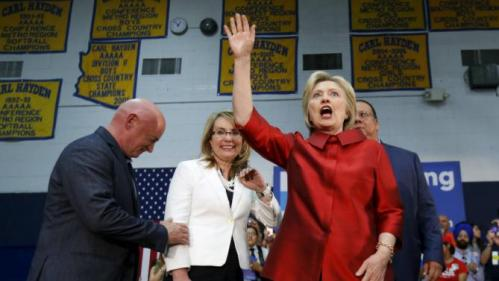 Democratic U.S. presidential candidate Hillary Clinton waves, as former U.S. Representative Gabby Giffords (D-AZ) and her husband Mark Kelly stand nearby, at a campaign rally at Carl Hayden Community High School in Phoenix, Arizona March 21, 2016. REUTERS/Mario Anzuoni