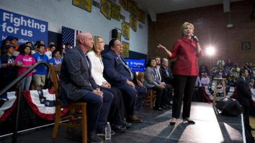 Democratic presidential candidate Hillary Clinton speaks at a campaign event at Carl Hayden Community High School in Phoenix, Monday, March 21, 2016. On stage with Clinton from left are Former Rep. Gabrielle Giffords, and her husband astronaut Mark Kelly, Governor of the Gila River Indian Community Stephen Roe Lewis, labor leader Dolores Huerta, and Rep. Ruben Gallego, D-Ariz., and Labor Secretary Thomas Perez. (AP Photo/Carolyn Kaster)