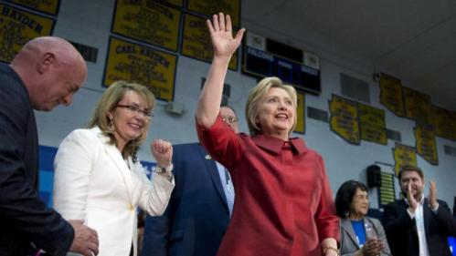 Democratic presidential candidate Hillary Clinton waves as she arrives at a campaign event at Carl Hayden Community High School in Phoenix, Monday, March 21, 2016. With Clinton on stage from left are former Rep. Gabrielle Giffords, and her husband Mark Kelly, Governor of the Gila River Indian Community Stephen Roe Lewis, labor leader Dolores Huerta, and Rep. Ruben Gallego, D-Ariz.(AP Photo/Carolyn Kaster)
