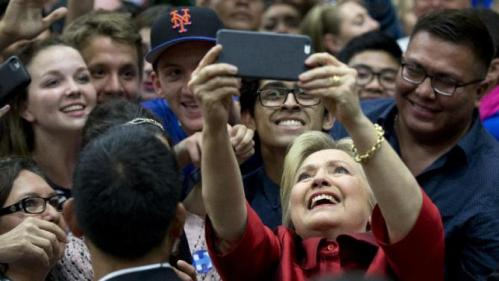 Democratic presidential candidate Hillary Clinton takes photos with people in the audience after speaking during a campaign event at Carl Hayden Community High School in Phoenix, Monday, March 21, 2016. (AP Photo/Carolyn Kaster)