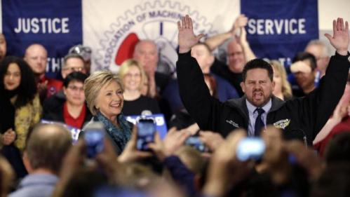 Democratic presidential candidate Hillary Clinton, left, is introduced by Boeing Machinists' union local president Jon Holden at a campaign event at the Boeing Machinists' union hall Tuesday, March 22, 2016, in Everett, Wash. (AP Photo/Elaine Thompson)