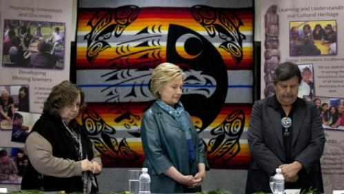 Democratic presidential candidate Hillary Clinton stands for a moment of silence for the victims of the attacks in Brussels, Belgium, with Puyallup tribal members Rollen Hargrove, left, and Bill Sterud, right, during a roundtable with Washington Tribal Leaders at Chief Leschi School in Puyallup, Wash., Tuesday, March 22, 2016. (AP Photo/Carolyn Kaster)