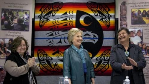 Democratic presidential candidate Hillary Clinton is applauded by Puyallup tribal members Rollen Hargrove, left, and Bill Sterud, right, during a roundtable with Washington Tribal Leaders at Chief Leschi School in Puyallup, Wash., Tuesday, March 22, 2016. (AP Photo/Carolyn Kaster)