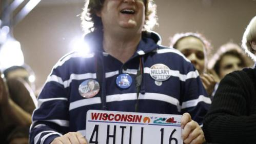 A supporter holds a license plate as he listens to Democratic presidential candidate Hillary Clinton speak at the Mary Ryan Boys and Girls Club in Milwaukee, Wis., Monday, March 28, 2016. (AP Photo/Patrick Semansky)