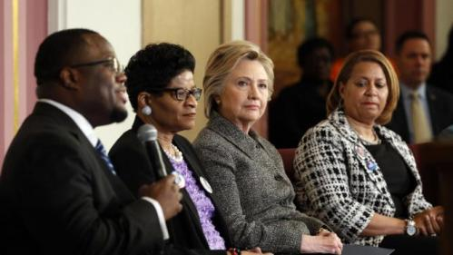 Democratic presidential candidate Hillary Clinton attends a forum on gun violence, Tuesday, March 29, 2016, at the Tabernacle Community Baptist Church in Milwaukee. From left are, Pastor Don Darius Butler, Geneva Reed-Veal and Annette Holt. (AP Photo/Patrick Semansky)