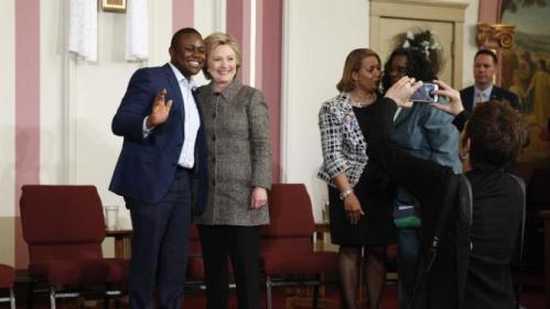 Patrice Achu, left, a naturalized U.S. citizen who grew up in Cameroon and said he will cast his first vote as a citizen for Clinton, poses for a photo with Democratic presidential candidate Hillary Clinton after a forum on gun violence, Tuesday, March 29, 2016, at the Tabernacle Community Baptist Church in Milwaukee. (AP Photo/Patrick Semansky)