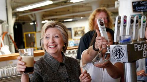 Democratic presidential candidate Hillary Clinton hoists a beer during a tour of at Pearl Street Brewery in La Crosse, Wis., Tuesday, March 29, 2016. (AP Photo/Patrick Semansky)