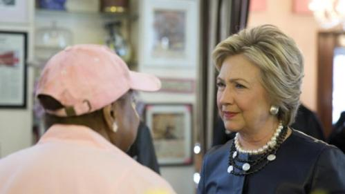 Democratic presidential candidate Hillary Clinton, right, meets a member of the community, during a campaign stop at the Make My Cake bakery, Wednesday, March 30, 2016, in the Harlem neighborhood of New York. (AP Photo/Mary Altaffer)