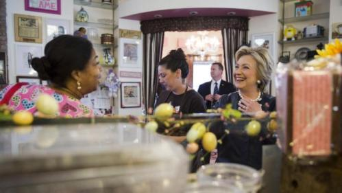 Democratic presidential candidate Hillary Clinton, right, meets a member of the community, left, at Make My Cake Bakery, Wednesday, March 30, 2016, in the Harlem neighborhood of New York. (AP Photo/Mary Altaffer)