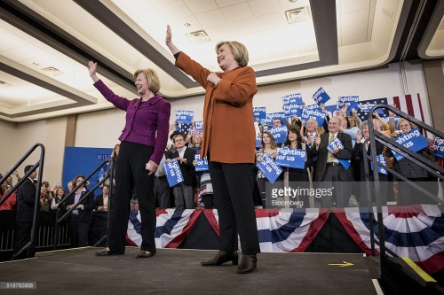 Hillary Clinton, former Secretary of State and 2016 Democratic presidential candidate, right, and Senator Tammy Baldwin, a Democrat from Wisconsin, wave during a campaign event in Eau Claire, Wisconsin, U.S., on Saturday, April 2, 2016. Clinton used Donald Trump's remarks about punishing women who have abortions if the procedure were outlawed to level a double-barreled attack on the Republican front-runner as well as her Democratic rival, Bernie Sanders. Photographer: Christopher Dilts/Bloomberg *** Local Caption *** Hillary Clinton; Tammy Baldwin