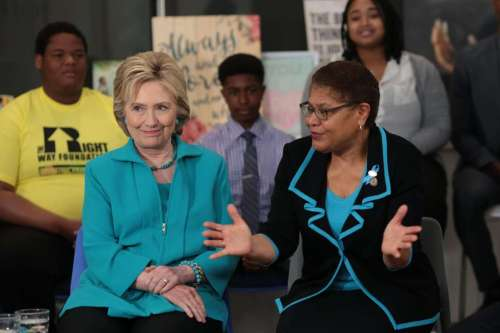 © Monica Almeida/The New York Times Hillary Clinton and Representative Karen Bass of Los Angeles gathered with a group of families and residents to discuss foster care at a union headquarters in…