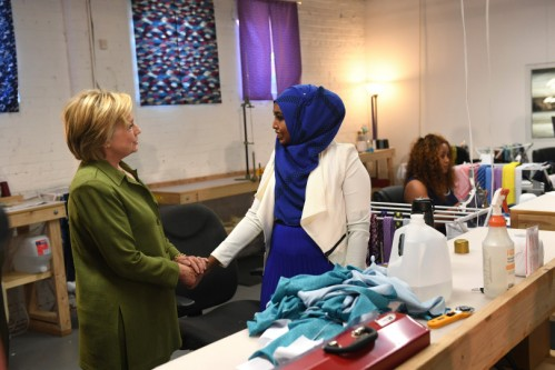 DENVER, CO - AUGUST 3: Democratic presidential nominee Hillary Clinton, left, meets with seamstress Hibo Webliye, right, as she works on sewing fabric at Knotty Tie Company on August 3, 2016 in Denver, Colorado. The company makes it's custom ties, scarves and bowties in the United States while employing legal immigrants from all over the world. The company seeks to build and create meaningful employment opportunities for resettled refugees. Webliye is a refugee from Somalia. (Photo by Helen H. Richardson/The Denver Post)