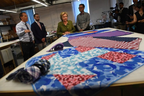 DENVER, CO - AUGUST 3: Democratic presidential nominee Hillary Clinton, middle, looks at scarves at Knotty Tie Company with co-founders Mark Johnson, right, and Jeremy Priest, second from left, and Austin Allan, left, merchandising director, on August 3, 2016 in Denver, Colorado. The company makes it's custom ties, scarves and bowties in the United States while employing legal immigrants from all over the world. The company seeks to build and create meaningful employment opportunities for resettled refugees. (Photo by Helen H. Richardson/The Denver Post)