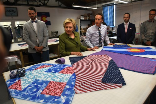 DENVER, CO - AUGUST 3: Democratic presidential nominee Hillary Clinton, middle, looks at scarves at Knotty Tie Company with co-founders Mark Johnson, far right, and Jeremy Priest, second from right, and Austin Allan, merchandising director, third from right, on August 3, 2016 in Denver, Colorado. The company makes it's custom ties, scarves and bowties in the United States while employing legal immigrants from all over the world. The company seeks to build and create meaningful employment opportunities for resettled refugees. (Photo by Helen H. Richardson/The Denver Post)