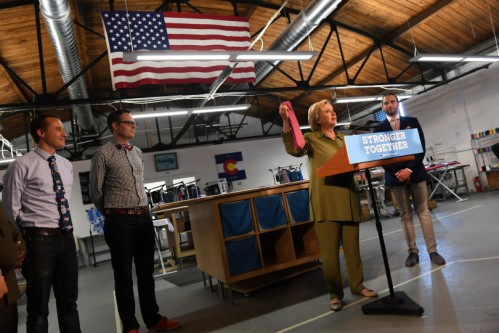DENVER, CO - AUGUST 3: Democratic nominee Hillary Clinton holds up a tie made in the USA by The Knotty Tie Company on August 3, 2016 in Denver, Colorado. Clinton visited the Colorado company while on the campaign trail. The company makes it's custom ties, scarves and bowties in the United States while employing legal immigrants from all over the world. The company seeks to build and create meaningful employment opportunities for resettled refugees. In the picture is Austin Allan, merchandising director, co-founder Mark Johnson, second from left, and Jeremy Priest, right, cofounder. (Photo by Helen H. Richardson/The Denver Post)