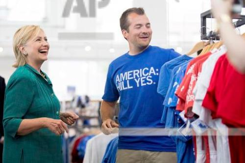 Democratic presidential candidate Hillary Clinton, left, speaks with owner and founder Mike Draper, right, as she tours Raygun, a printing, design & clothing company, in Des Moines, Wednesday, Aug. 10, 2016. (AP Photo/Andrew Harnik)