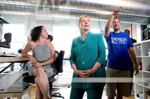 Democratic presidential candidate Hillary Clinton, center, accompanied by owner and founder Mike Draper, right, tours Raygun, a printing, design & clothing company, in Des Moines, Wednesday, Aug. 10, 2016. (AP Photo/Andrew Harnik)