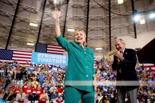 Democratic presidential candidate Hillary Clinton, accompanied by Former Sen. Tom Harkin, D-Iowa, right, waves as she arrives to speak at a rally at Abraham Lincoln High School, in Des Moines, Wednesday, Aug. 10, 2016. (AP Photo/Andrew Harnik)
