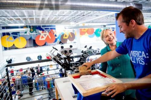 Democratic presidential candidate Hillary Clinton smiles as owner and founder Mike Draper, right, shows her how they silk screen shirts as she tours Raygun, a printing, design & clothing company, in Des Moines, Wednesday, Aug. 10, 2016. (AP Photo/Andrew Harnik)