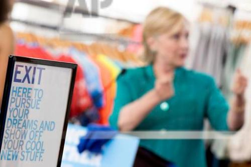 "A sign reads ""Exit here to pursue your dreams and show off your cool new stuff"" as Democratic presidential candidate Hillary Clinton speaks after touring Raygun, a printing, design & clothing company, in Des Moines, Wednesday, Aug. 10, 2016. (AP Photo/Andrew Harnik)"