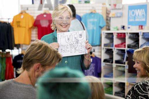 "Democratic presidential candidate Hillary Clinton holds up a sign a girl gave her that reads ""Future President"" as she tours Raygun, a printing, design & clothing company, in Des Moines, Wednesday, Aug. 10, 2016. (AP Photo/Andrew Harnik)"