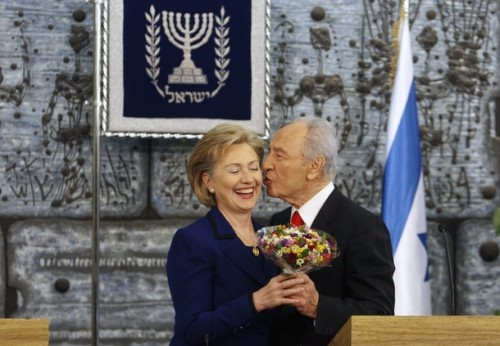 Israel's President Shimon Peres (R) kisses U.S. Secretary of State Hillary Clinton as he gives her flowers after their meeting in Jerusalem March 3, 2009. Clinton pledged on Tuesday to press for Palestinian statehood, putting Washington on a possible collision course with Israeli Prime Minister-designate Benjamin Netanyahu. REUTERS/Ammar Awad (JERUSALEM)